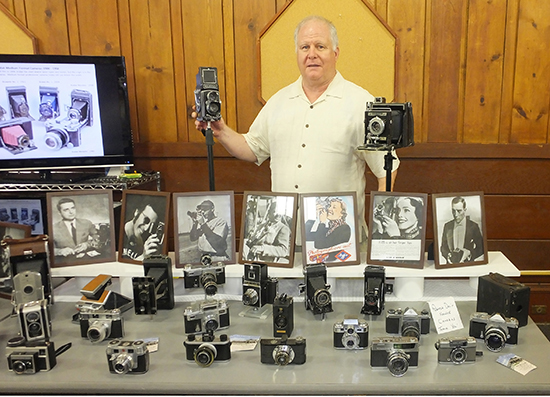 Kevin Murray and his extensive antique camera collection.